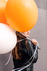 Close up of girl hiding face balloons.
