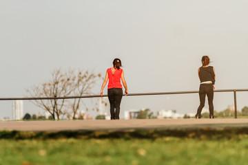 Two women skating on roller skates at a skatepark