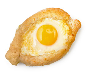 Caucasian delicious Ajarian khachapuri in shape of boat with egg isolated on white background, top view.
