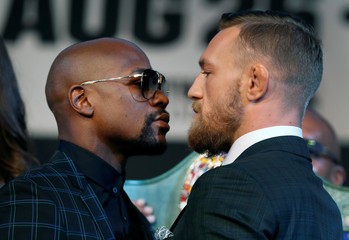 Undefeated boxer Floyd Mayweather Jr. (L) of the U.S. and Conor McGregor of Ireland face off during a news conference in Las Vegas