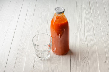 A bottle of carrot juice and an empty glass on an empty white wooden table