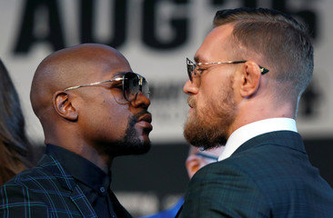 Undefeated boxer Floyd Mayweather Jr. (L) of the U.S. and UFC lightweight champion Conor McGregor of Ireland face off during a news conference in Las Vegas