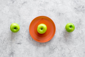 Slimming diet. Apple at plate on grey stone background top view copyspace