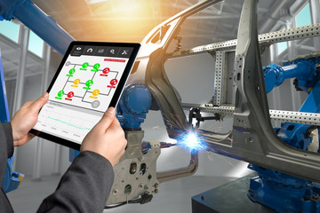 Male manager hand use tablet for check real time vibration analysis monitoring system application in smart factory. Automobile manufacturing production machine , robot arm. industry 4.0 concept.
