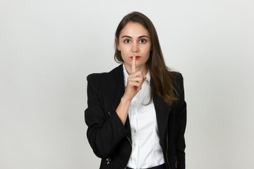 Young young businesswoman holding a finger on her lips - silent gesture.