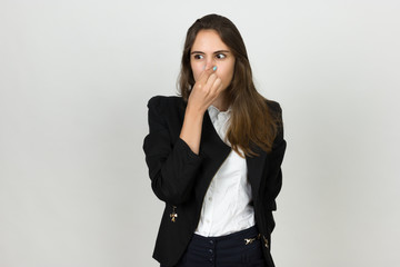 Young businesswoman holding her nose because of a bad smell