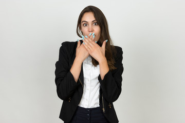 Portrait of a pretty young businesswoman covering her mouth