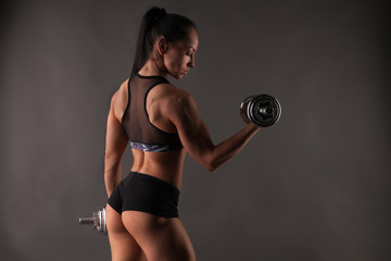 Muscular beautiful fitness model woman athlete standing posing in sportswear top and shorts, doing workout with high weight dumbbells. Copy space. Healthy life bodybuilding lifestyle concept image.