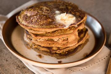 Pumpkin pancakes with a pad of butter sprinkled with nutmeg
