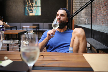 Hipster drinking wine in cafe