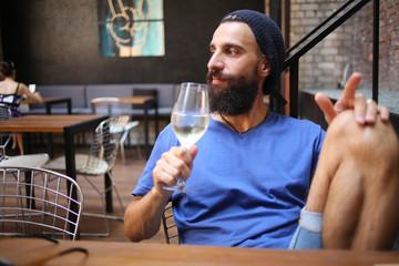 Bearded man with wine looking away