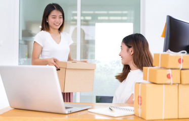 Young asian girl together freelancer business private working at home office holding packaging box for checking product delivery online market on purchase orders to customer.