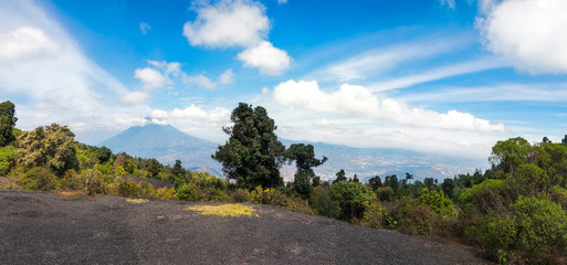 Panoramic View of Volcano Aqua, as almost always surrounded by clouds from the trail climbing towards Volcano Pacaya in Guatemala.