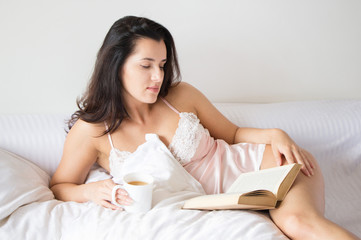 Beautiful young girl reading a book on bed
