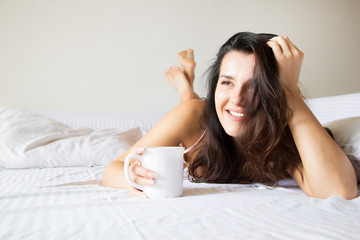 Young beautiful girl on the bed drinking coffee