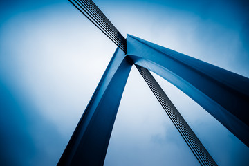 low angle view of silver steel bridge against sky.