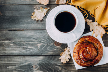 Fresh Pastry Bun, Cup of hot coffee and autumn leaves on wooden background. Top view, copy space