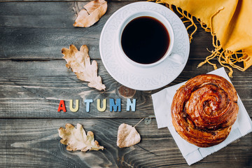 Fresh Pastry Bun, Cup of hot coffee and autumn leaves on wooden background. Wooden letters wod AUTUMN. Top view, copy space