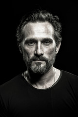 Monochrome portrait of strong mature beardy man. Male with severe look on his face.