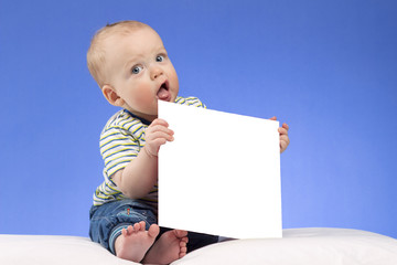Funnt infant kid with white piece of paper on the blue background. Cute toddler with mock-up. Stufio shot with copy space