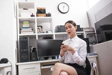 Business woman sitting in office and using smartphone.