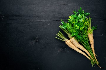 Parsley. Root parsley. On a wooden background. Top view. Free space for text.
