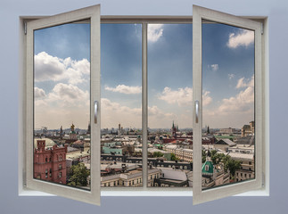 A view through an open window in the interior. Moscow urban landscape with a blue sky and light clouds.
