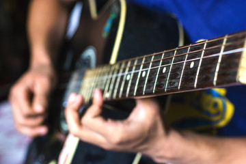 blurred background of a guy wearing blue T-shirt playing his guitar
