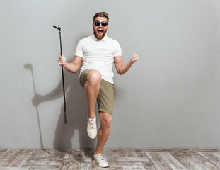 Full length image of a Happy Screaming golfer in sunglasses