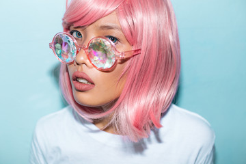 Asian pink hair woman portrait with kaleidoscope glasses and unicorn queen shirt