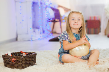 Little girl with huge christmas tree ball