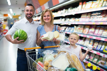 Young parents with child shopping in hypermarket