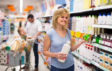 woman picking bottle with shampoo from shelf in cosmetics section in shop