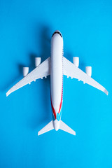 Miniature toy airplane on blue background. Trip by airplane