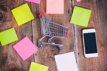 Shopping Cart, mobile phone and paper notes on wooden background