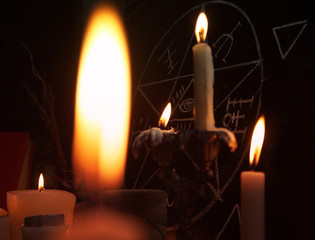 Burning candles and pentagram symbol on the board. Halloween and occult concept.