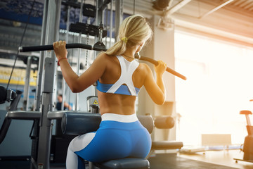 Beautiful sports young woman posing in fitness gym. Fitness girl in blue sportswear. Muscular blonde fitness woman doing exercises For Back On Machine. Sport - concept of healthy lifestyle.