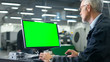 Senior engineer in glasses is working on a desktop computer with a green screen on monitor in a factory.