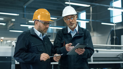 Two engineers in hardhats discuss information on a tablet computer while standing in a factory.