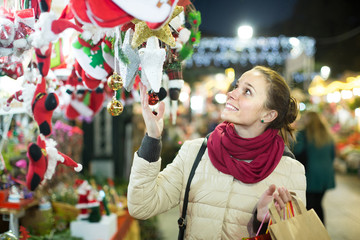 woman choosing Christmas decoration at market in evening time