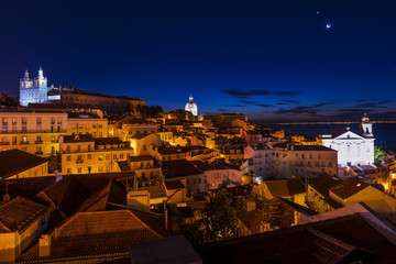 View of the Alfama neighborhood from the Portas do Sol viewpoint at night in Lisbon, Portugal; Concept for travel in Portugal