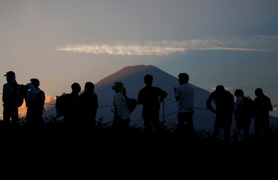 Spectators wait for arrival of a shuttle bus for leaving at Japanese Ground Self-Defense Force's Higashifuji training field as Mount Fuji is seen on background in Gotemba