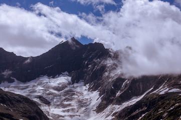 Wolken vor verschneiten Bergen