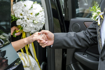 Groom holds the bride's hand out of the car