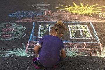 Girl draw house on asphalt