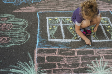 Girl draw house with chalk on asphalt
