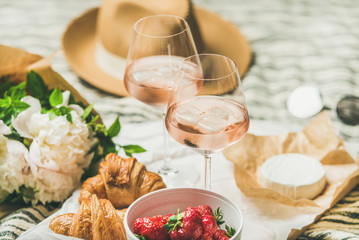 Foto op Canvas Picknick French style romantic summer picnic setting. Flat-lay of glasses of rose wine with ice, fresh strawberries, croissants, brie cheese, straw hat, sunglasses, peony flowers. Outdoor gathering concept