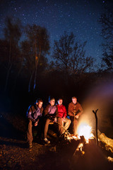 Long exposure photo of four hikers sitting around bonfire and warming at night autumn forest with starry sky on background. Tourists are preparing their dinner on fire.