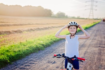 Boy child in white bicycle helmet riding on bicycle