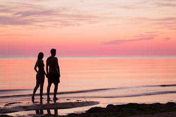 Young couple walking at the seaside in summer evening. Man's and woman's silhouettes on the beach. Sea water reflecting a pink heavenly colors and creating a romantic atmosphere.